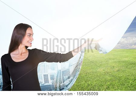Smiling young woman dragging abstract cloth with city image and revealing green meadow. Eco and nature concept