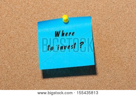 Where to invest question writing qestion on blue sticker pinned at notice board.