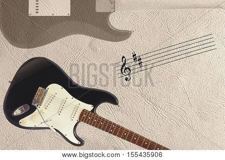 Stave and solid body classic electric guitar and back of guitar body at the bottom of the light skin background.