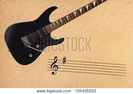 Stave and black electric rock guitar at the top of the rough cardboard background.