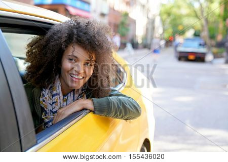 Cheerful girl riding a New York City taxi cab