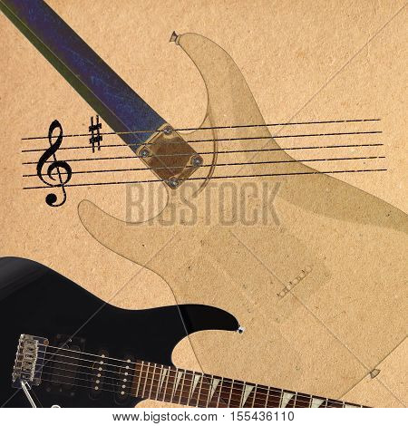 Notes and black electric rock guitar and back of guitar body on the rough cardboard background.