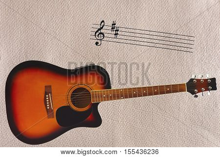 Notes stave and acoustic sunburst guitar at the bottom of the rough cardboard background.