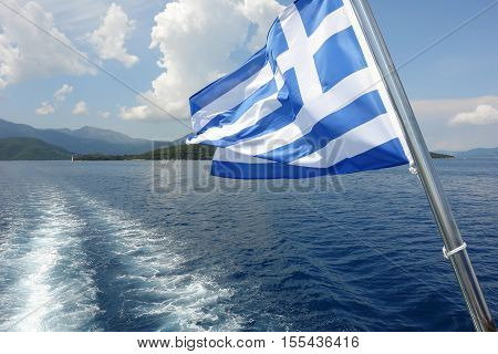 Levkas GREECE May 11 2013: Panoramic view with Greek flag blue sea and mountains in Ionian sea Greece.