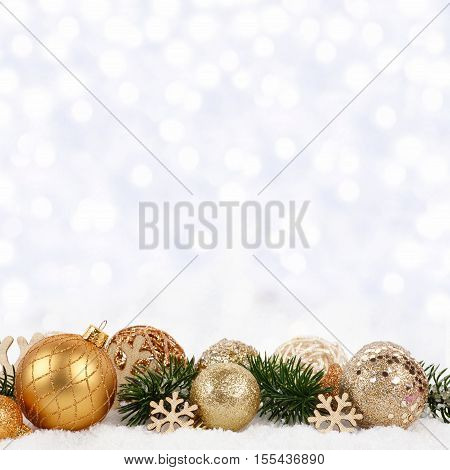 Golden Christmas Ornaments And Branches In Snow With Twinkling Silver Background