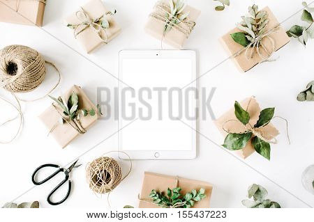 tablet with mock up screen and beauty arrangement frame of craft boxes and green branches on white background. flat lay top view