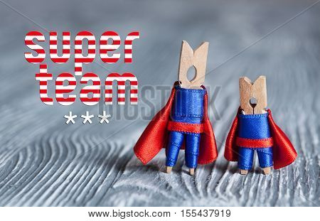 Super team concept. Clothespin peg superheroes in blue suit and red cape. Gray wood abstract design background. macro