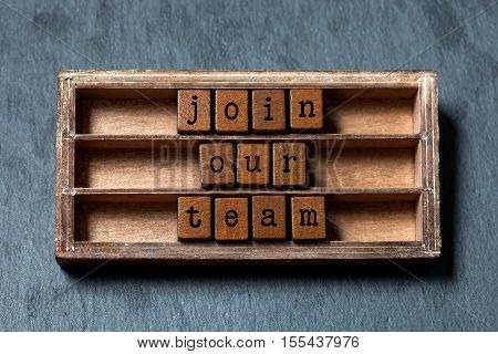 Join our team conceptual image. Vintage blocks with text in wooden box. Gray stone background, soft focus