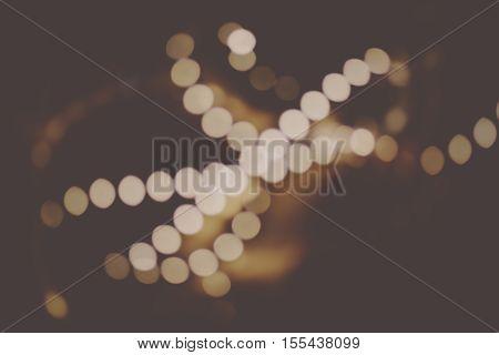 Vintage blur bokeh defocused on dark brown background. Abstract de-focused blurred rear retro gold background, christmas decorations in dark room out of focus shot.