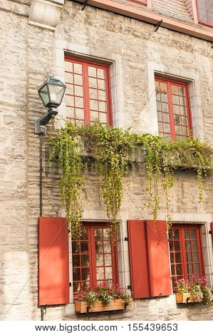 Old Quebec City facade with red windows and flower beds