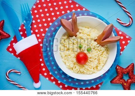 Creative idea for kids Christmas food - couscous with vegetables shaped Christmas deer festive table with decorations