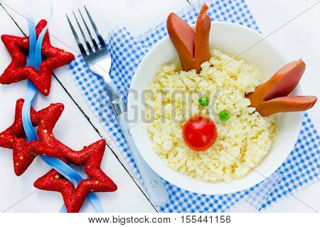 Christmas dinner for kids - couscous with green peas sausage and cherry tomato shaped Christmas deer