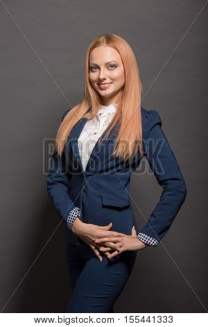 Picture of young beautiful business woman smiling for camera while posing for photographer isolated on grey background in studio.