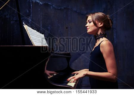 Mid side shot of a satisfied smile of charming attractive female while playing the piano isolated in studio