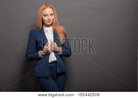 Portrait of cheerful professional vogue model woman with long red hair posing for fashion magazine isolated on grey background in studio.