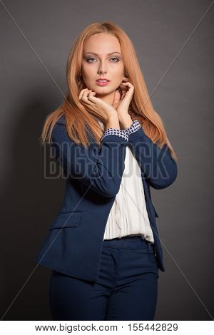Pretty professional model woman posing in navy blue costume or suit in studio. Red haired lady touching her hair while demonstrating her perfect makeup.