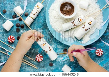 Child making snowman marshmallow pops kitchen composition for winter holiday. Funny food art idea for Christmas dessert treat top view