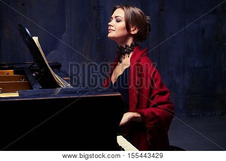 Side mid shot of cheerful young woman with stylish make-up and hair bun enjoys playing the piano. Enjoying the unity of melody and harmony