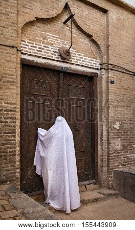 Woman in white Veil knocking on the old ornate wooden door of a building in city of Yazd Iran.