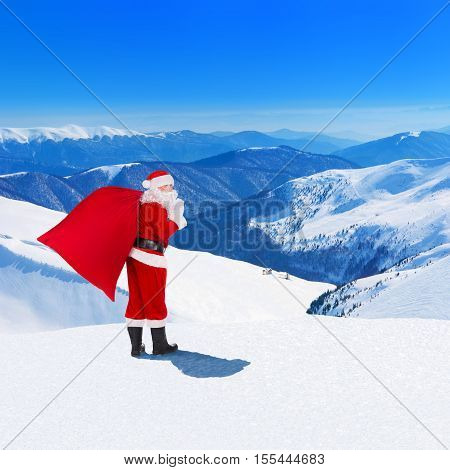 Santa Claus with large merry Christmas sack full of gifts against snowy winter mountains landscape and houses forest and blue sky New Year holiday concept