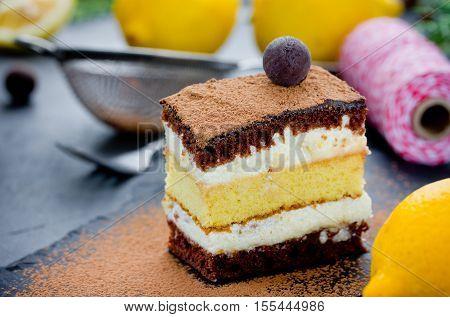 Piece of layer chocolate truffle lemon cake. Delicious sponge cake with cream on holiday