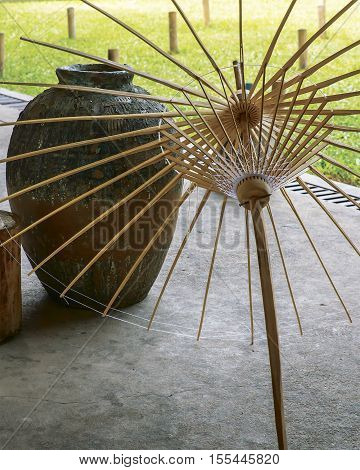 frames Asian bamboo umbrellas in a handicraft workshop in Thailand