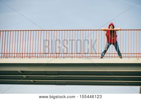 Young long haired girl leaning against railing on the urban bridge. Lifestyle funky in summer. Trendy sport teen wearing hood.