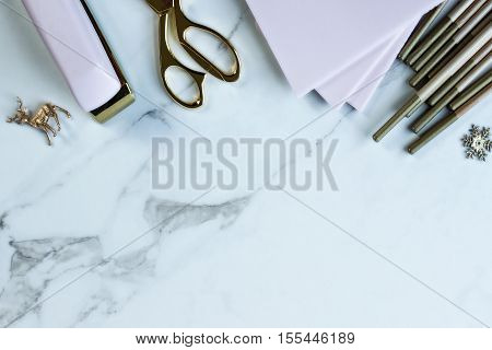Over head flat lay view of a marble desktop with pink and gold office supplies and Christmas trinkets
