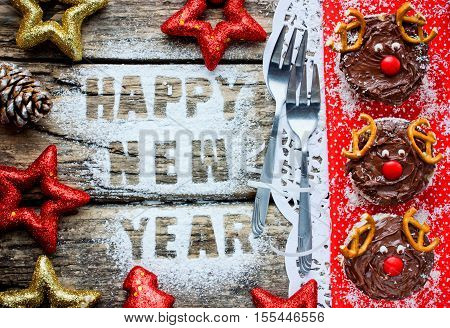 Happy New Year and Merry Christmas food background with greeting text festive decorations and cake deer top view