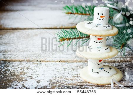 Christmas food background - cute melting snowmen cookies on snowy wooden background with Christmas tree branch blank space for text