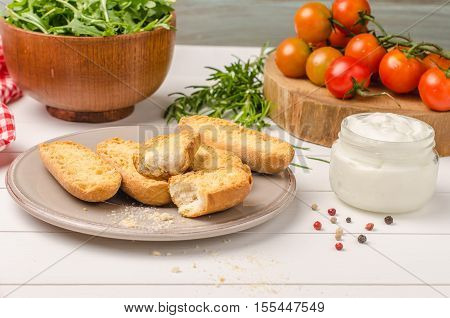 Vegetarian toasts with cream cheese tomatoes arugula rosemary and black pepper on rustic wooden table