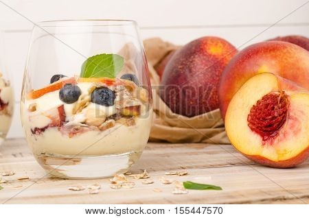 Granola with peaches yogurt and blueberries on wooden table
