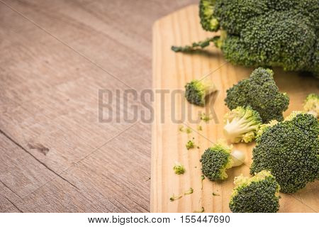 Fresh broccoli and knife on wooden table close up