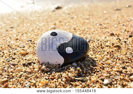 yin yang symbol painted on a rock on the sea beach