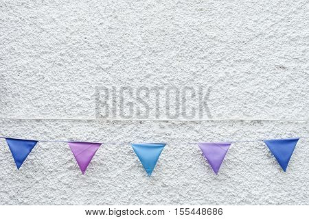 Colorful Party flags bunting hanging on white wall background. Minimal hipster style design.