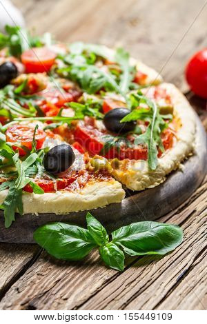 Fresh pizza made of fresh ingredients on old wooden table