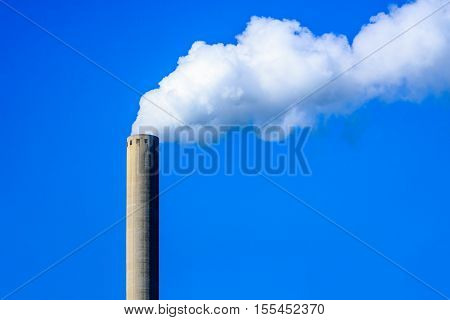 Colorful image of white smoke clouds from a high concrete chimney against a bright blue sky on a sunny day in the summer season.