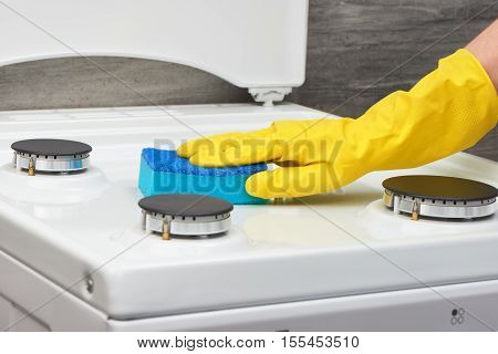 Hand In Yellow Glove Cleaning White Stove With Blue Sponge