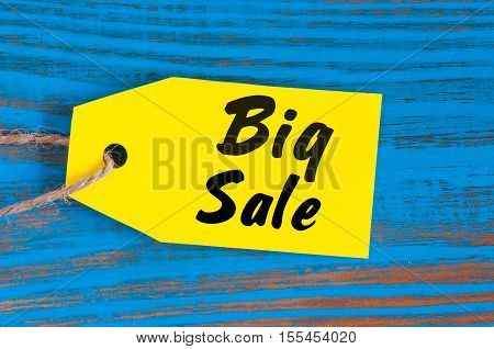 Big Sale tag on blue wooden background. Sales, discount, advertising, marketing price tags for clothes, furnishings, cars