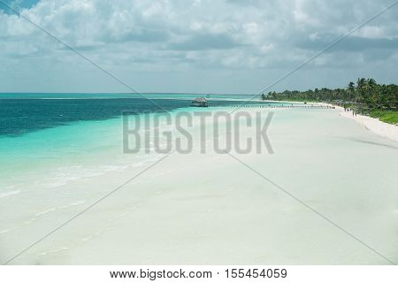 great amazing natural view of big white sandy tropical beach with people walking in the background