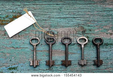 Door key with blank card for the text among other ones on old wooden background