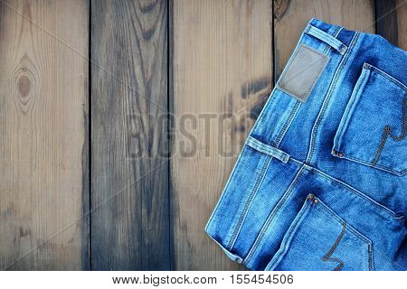 Blue jeans as casual wear on wooden background