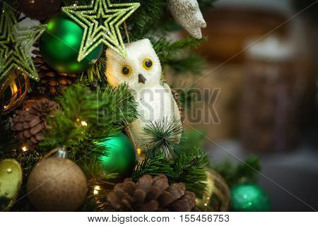 The Christmas tree is decorated with spheres, a star, an owl