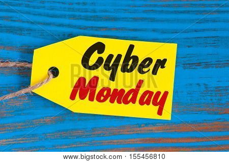 Cyber monday sales tag on blue wooden background.