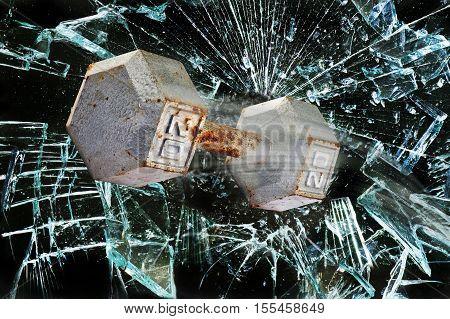 Dumbbell weight through a broken glass window.