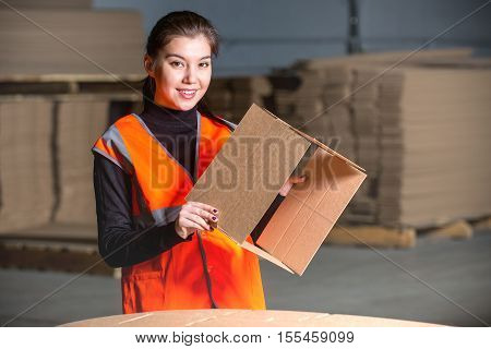 Paper mill factory female worker with new box in her hand