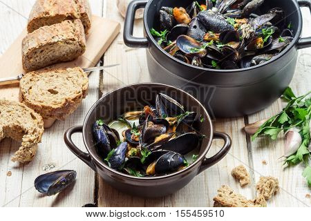 Mussels served with bread for dinner on old wooden table