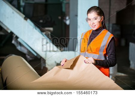 Paper mill factory worker checking paper quality