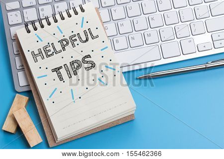 Word text Helpful tips on white paper on office table / business concept