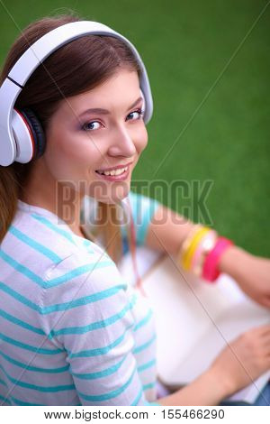 Woman listening to the music sitting on green grass